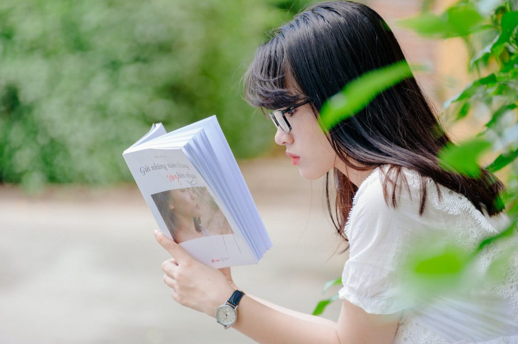 A girl is reading a book on her hand
