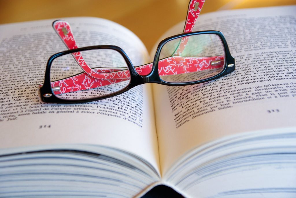 A glasses on a opened book